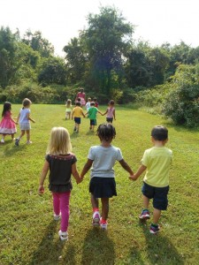 Children holding hands while others play outside.