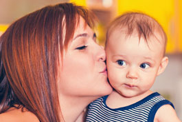 Mom affectionately kissing her wide-eyed baby on the cheek