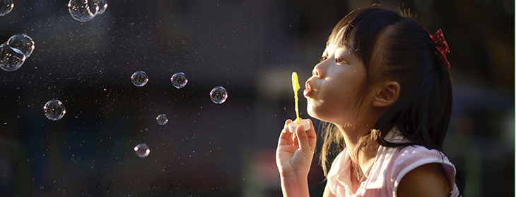Asian girl blowing bubbles.