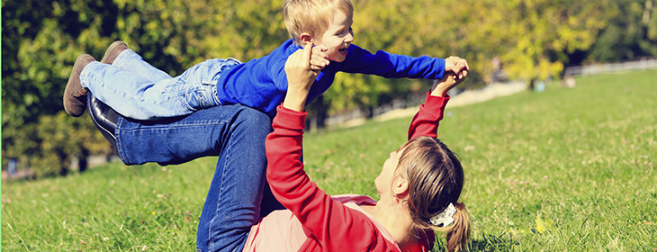 Mother and son playing outdoors in autumn park