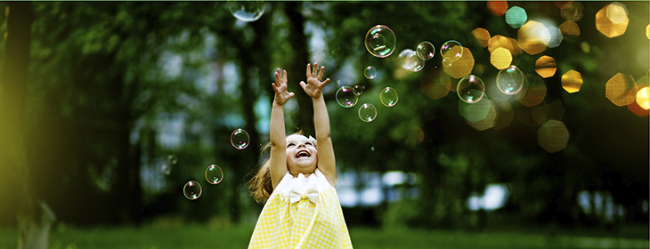Little girl reaching for bubbles in a meadow.