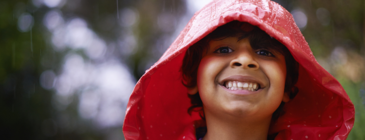 Shot of an enthusiastic little boy wearing a raincoat outside