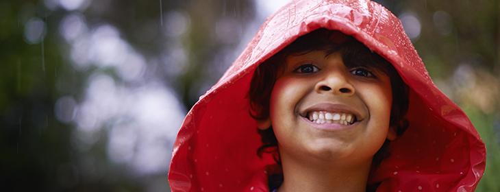 Shot of an enthusiastic little boy wearing a raincoat outside
