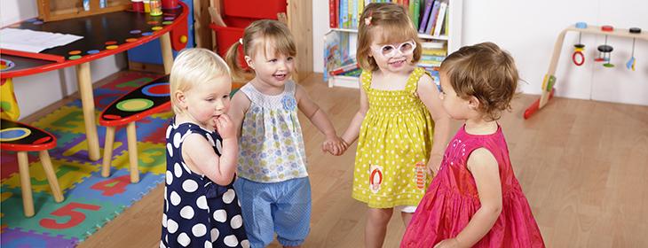 Four preschool girls holding hands in class