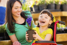 Laughing little girl in wheelchair holds lovely potted plant with a purple bloom as her smiling mom looks on