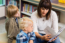 Mom pages through book in library as toddler watches intently and older child reads along beside her
