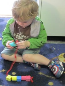 Boy toddler in a green jacket strings blocks through a red piece of string.