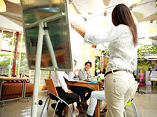 Group of people sitting around the table follow what woman is pointing out on white board stand