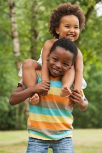 Young African American boy carries younger sibling on his back