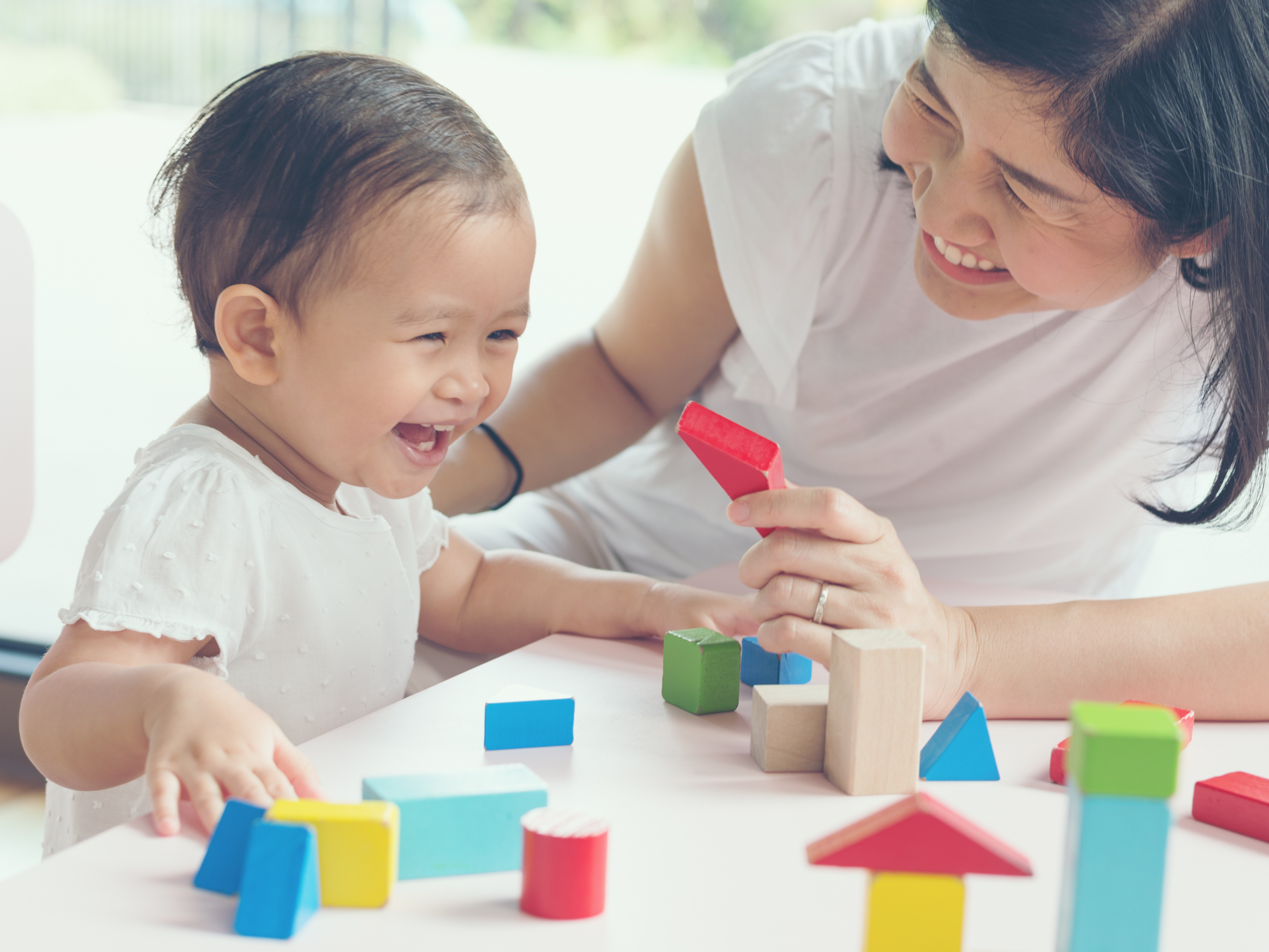 Asian mom and young daughter smiling playing with blocks