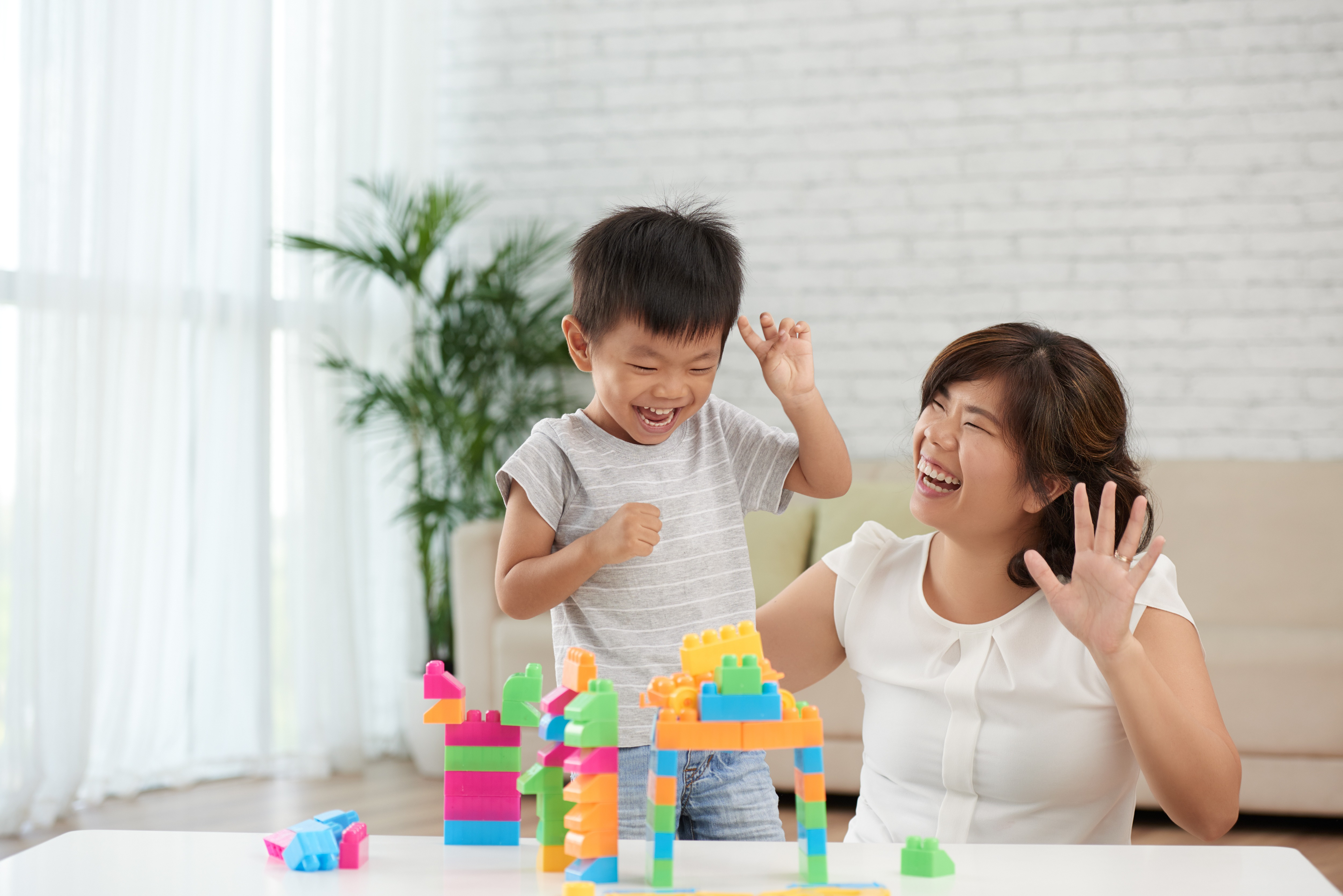 Asian little boy and his mother playing with blocks and having fun