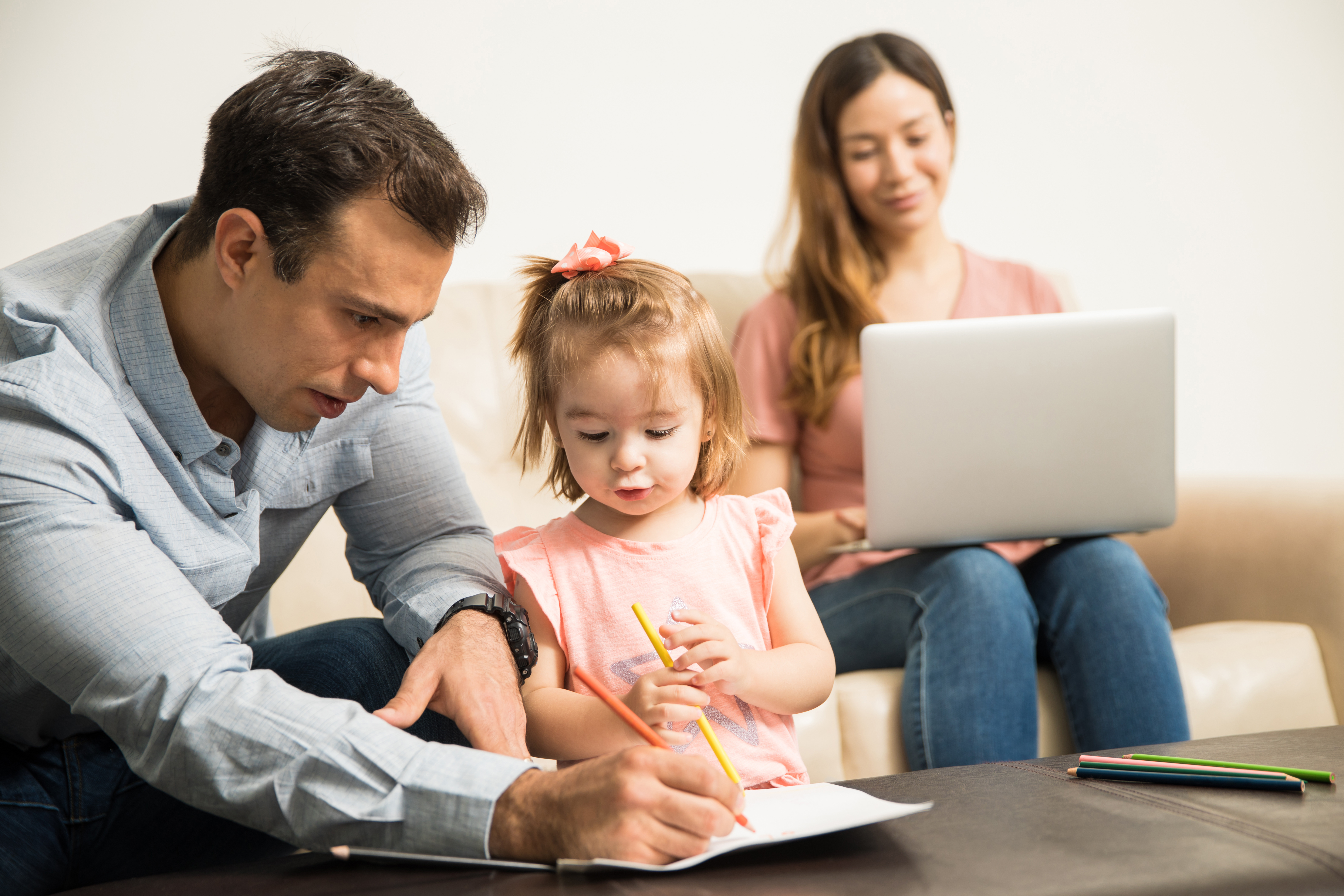 Latin dad drawing with her attentive daughter while her happy mom works in her laptop