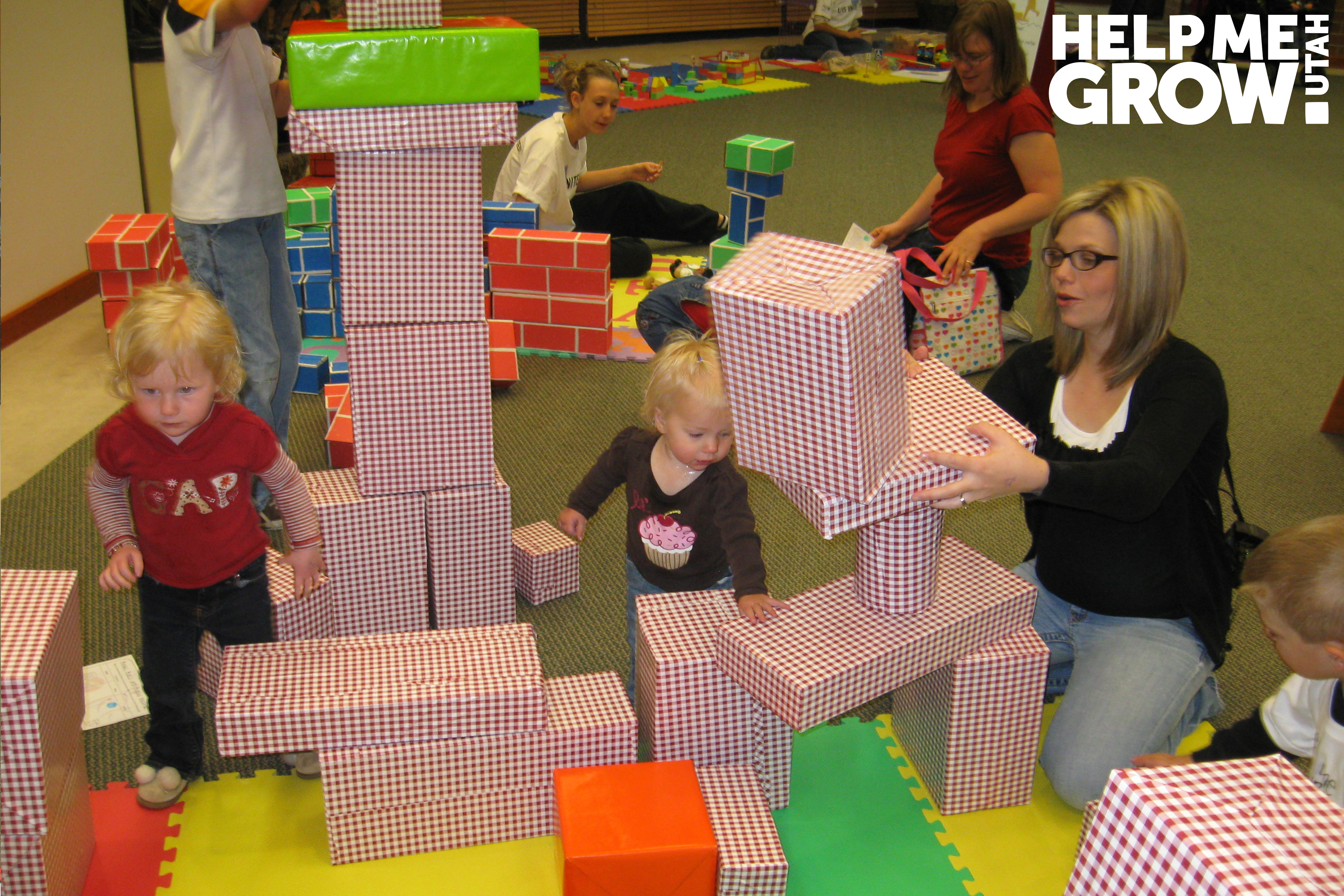 Mother and young daughter stack blocks together at a Books Blocks & Balls event in Utah
